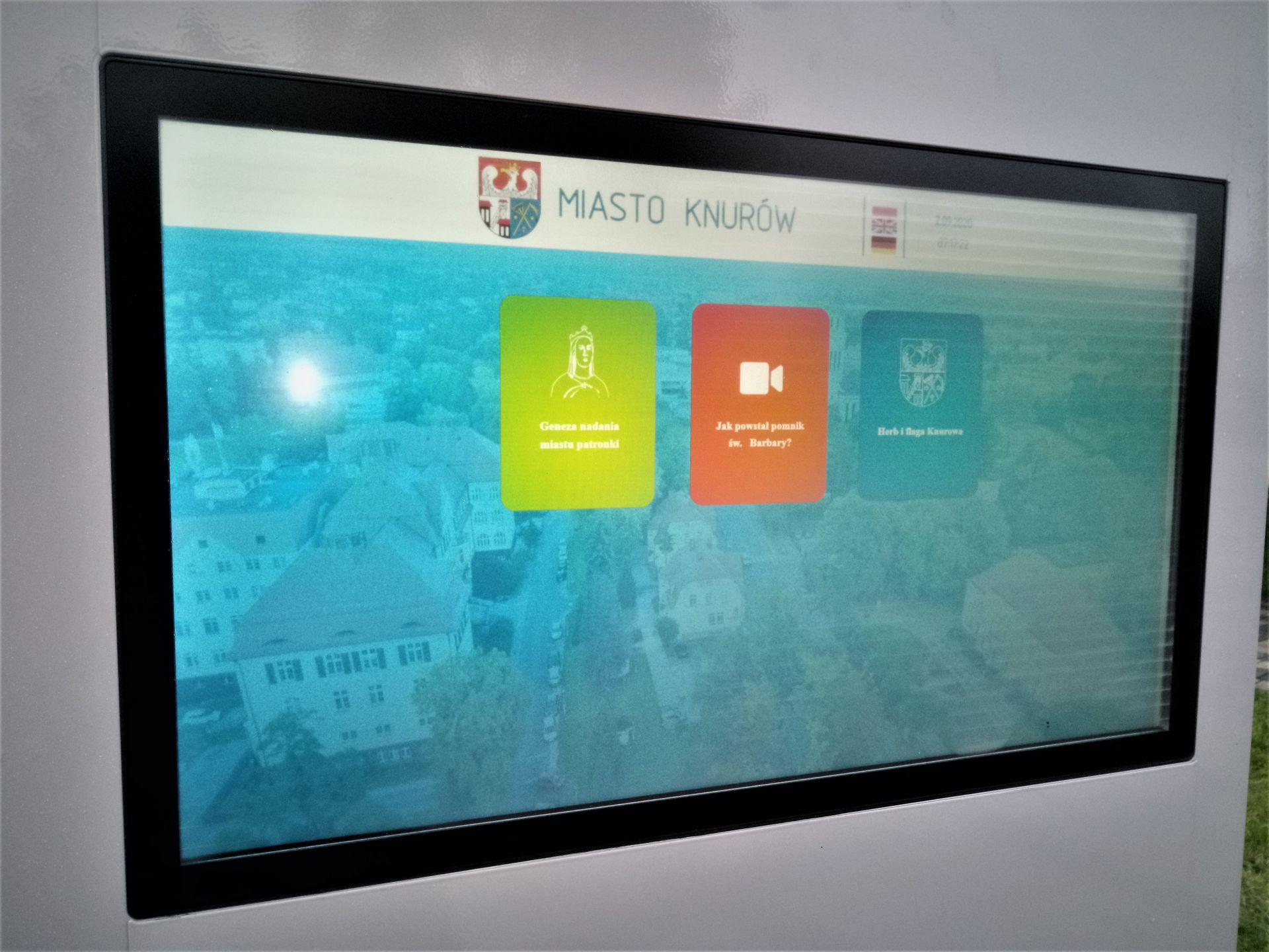 Infokiosk przedstawiający aplikację multimedialną przedstawiającą patronkę miasta oraz symole Knurowa